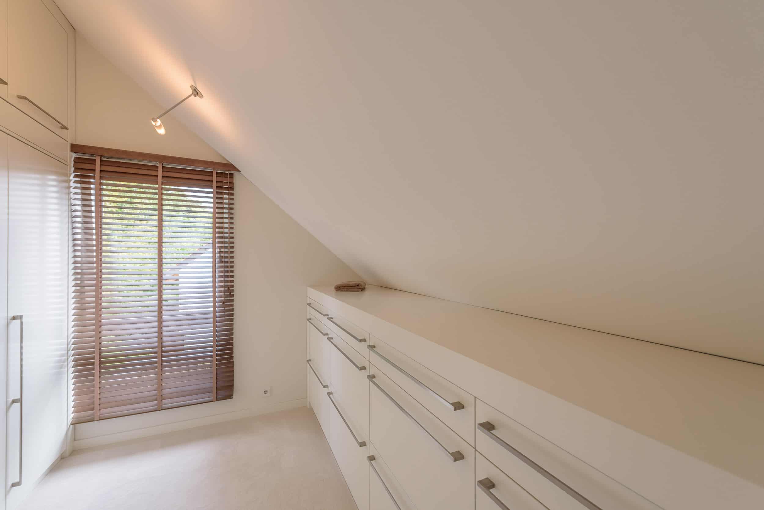 Ein komplettes Zimmer für die Ankleide mit stilvollen Einbauschränken und großen Spiegeln