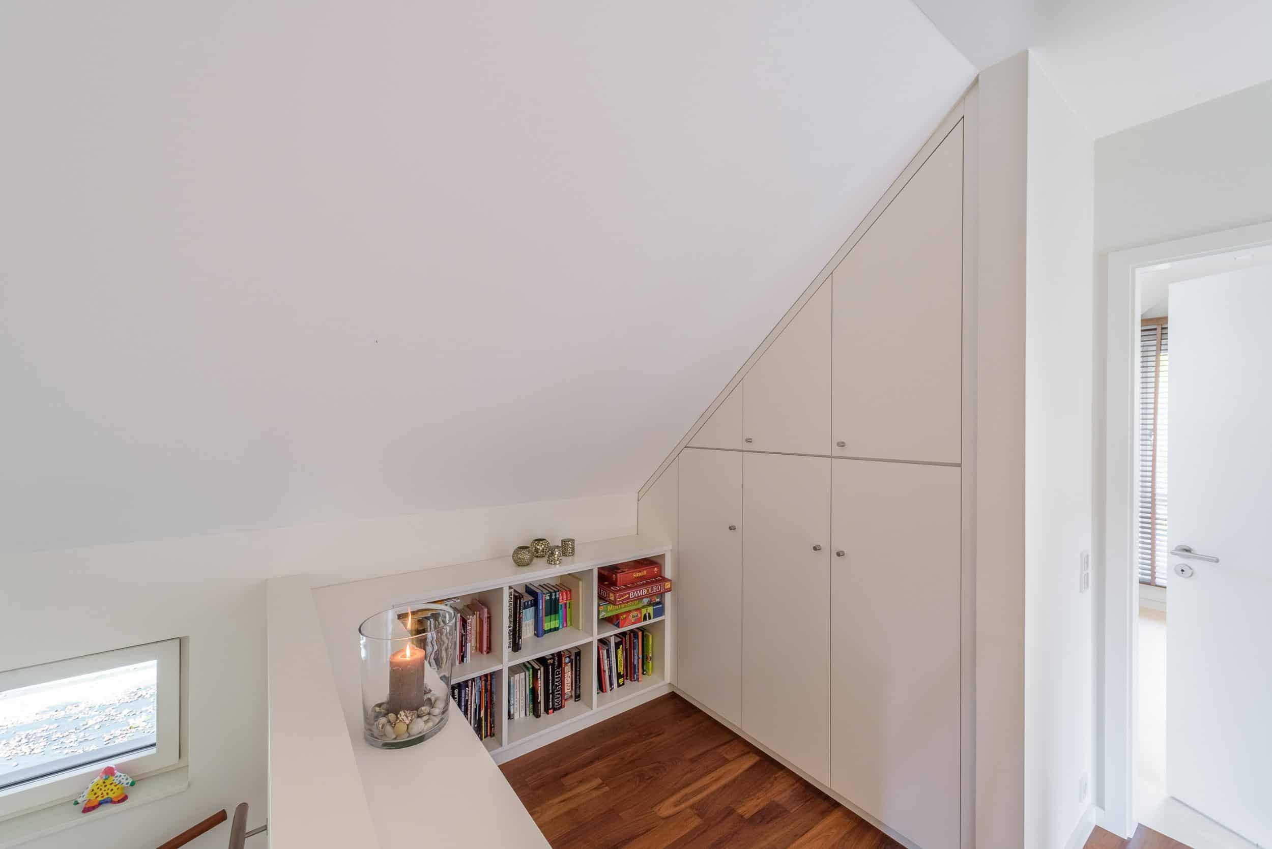 Flächenbündiger Einbauschrank und Bücherregal unter einer Dachschräge